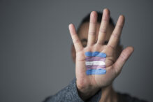 closeup of the palm of the hand of a young caucasian person with a transgender flag painted in it, in front of his or her face