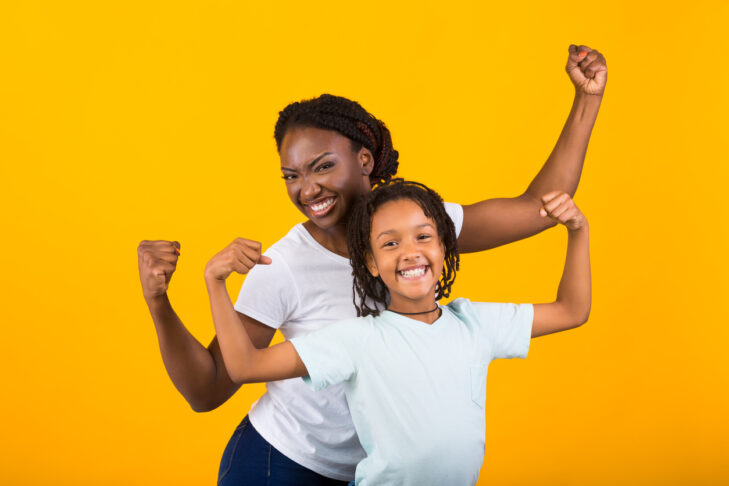 Celebrating Success. Cheerful black mother and daughter holding hands up for victory isolated on yellow background