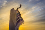 Man in a tallit, Jewish prayer shawl is blowing the shofar ram's horn