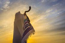 Man in a tallit, Jewish prayer shawl is blowing the shofar ram's horn