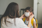 Image of Asian mother help her daughter wearing medical mask to prepare go to school. Avoiding Covid-19 or coronavirus outbreak.