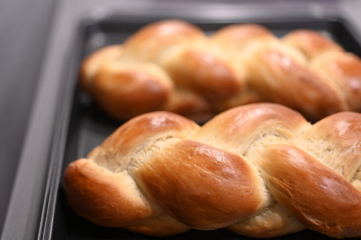 Close up of two cooked challah sweet bread on a baking tray.