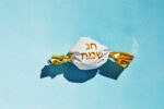 Candy cane with the inscription in Hebrew - Happy holiday. The concept of the Rosh Hashanah holiday - the Jewish New Year.