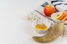 Rosh Hashana symbols, jewish new year. Apple and honey, prayer book, Shofar ram's horn, on white table. jewish holiday concept. Rosh Hashana postcard template. Selective focus.