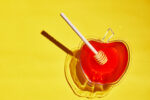 Bowl with honey and a wooden stick with a hard shadow on a yellow background. The concept of the Rosh Hashanah holiday - the Jewish New Year.