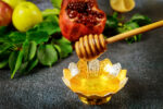 Natural sweet honey with wooden honey stick and pomegranate.