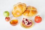 Round challah with pomegranates, apples and honey, traditional food eaten on Rosh Hashana, the Jewish New Year.
