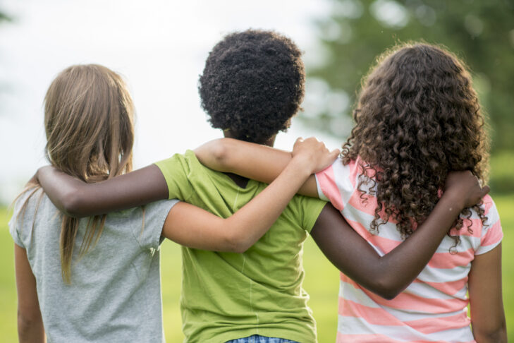 A rear view of a multi-ethnic group of elementary age girl friends are standing together with their arms around each other. They are looking out at the park on a spring day.
