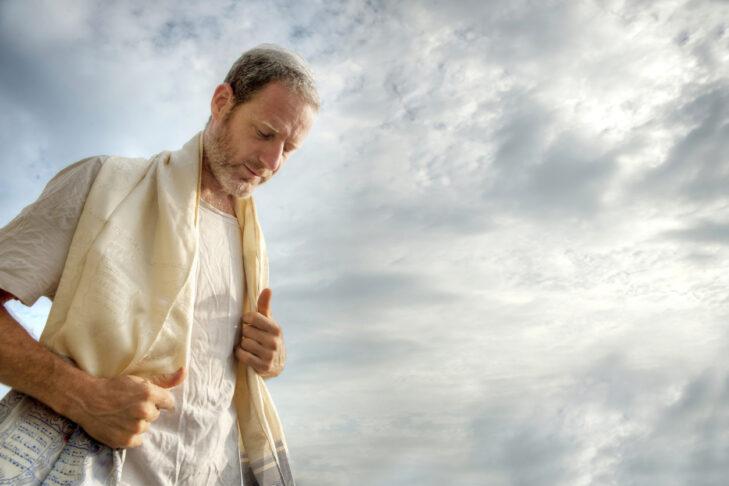 Jewish man engaged in morning prayers.