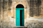 Italian house: a vibrant arched green door (ajar) in a mottled yellow house. Shot in Sicily.