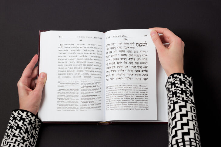 Jewish book, with woman's hand, on black background. Text of the Hebrew, prayer. Woman reading book