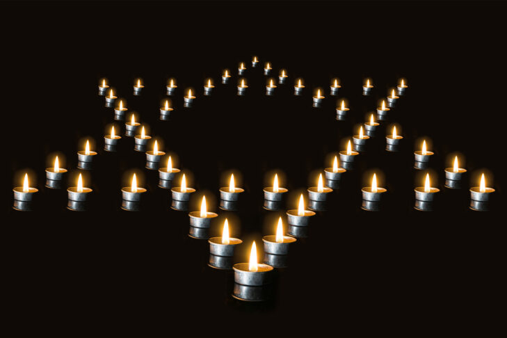 The star of David lined with candles in the night, on a black background. Burning candles - a symbol of International Holocaust Remembrance day 27 January