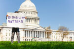 Child boy protest in front of the USA capitol in Washington holding sign saying disability matters