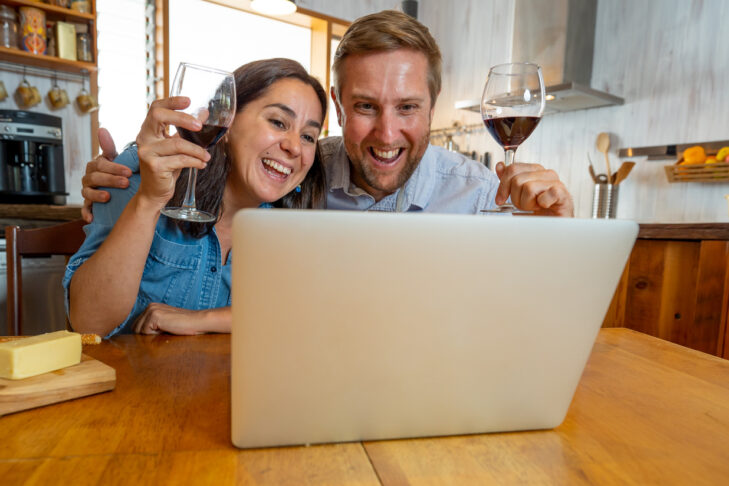 COVID-19 Network and Hope concept. Couple online chatting with friends cheering with wine celebrating easing of coronavirus restrictions. Man and woman video calling family using laptop at home.