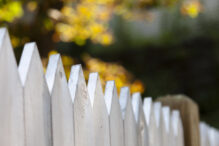 A white picket fence with short focus and an autumn background.