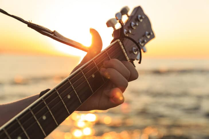 Young guy playing a guitar at sunset(Soft Focus)