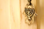 An antique (19th C) ornate silver Khamsa talisman pendant with Jewish menorah design hanging against a pale yellow background. Originally from the Sephardic community in North Africa. Plenty of copy space.