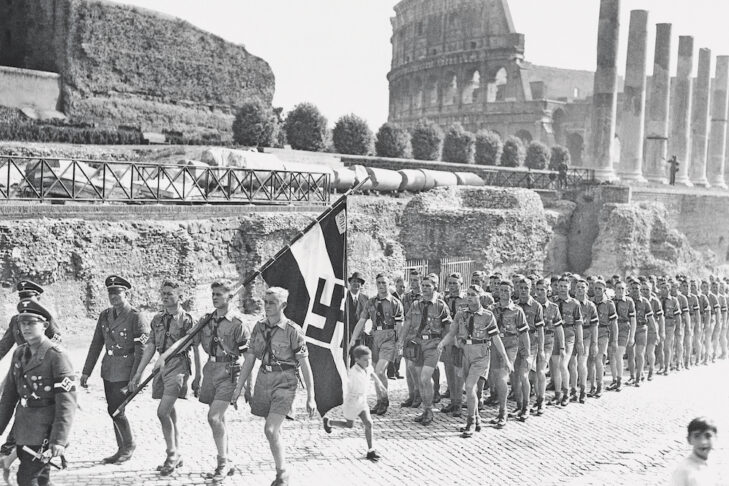 The Coliseum forms the background as a contingent of German Hitler Youth, carrying a Nazi banner, march through ancient Rome, Sept. 28, 1936. Taking advantage of the space between the standard bearer and the scouts, an Italian youngster darts across to a better vantage point. (AP Photo)
