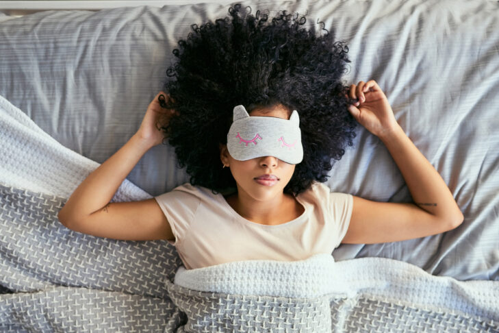 Shot of a young woman sleeping with a mask on in bed