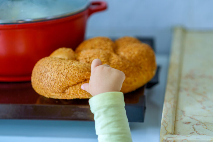 The hand of a hungry child hold and break a piece of bread. A kid's hand tearing a piece of challah. Hot plate for the Sabbath. Pot with traditional food and challah-special bread in Jewish cuisine.