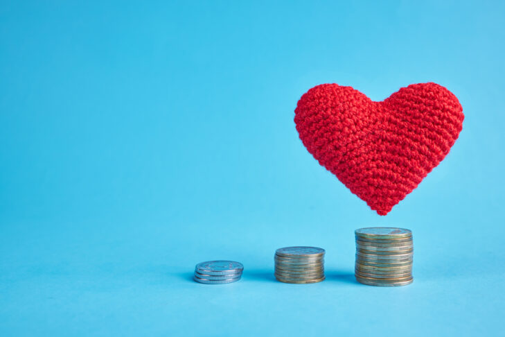 Red heart flying under coin stacks over the blue background. copy space. money coins stairs to love and romance concept. love to money concept.