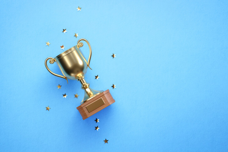 Star shaped confetti falling over gold cup sitting over blue background. Horizontal composition with copy space. Directly above.