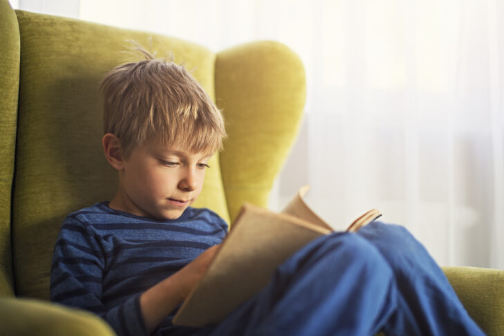 Little boy sitting on a gree armchair near the window, reading a book. The boy is aged 5 and is wearing blue clothes.