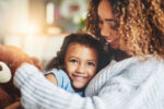 Shot of an adorable little girl and her mother in a warm embrace at home