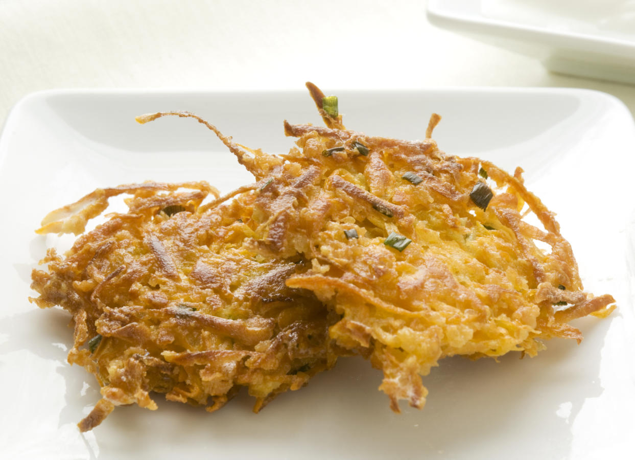 A closeup view of two sweet potato latkes on a white plate. The background is soft and creamy and shows off the wonderful orange colour and texture of the two latkes. The lighting is a natural light from a window behind and to the right in the image.