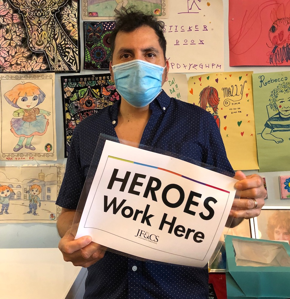 A Residential staff member holding a Heroes Work Here sign