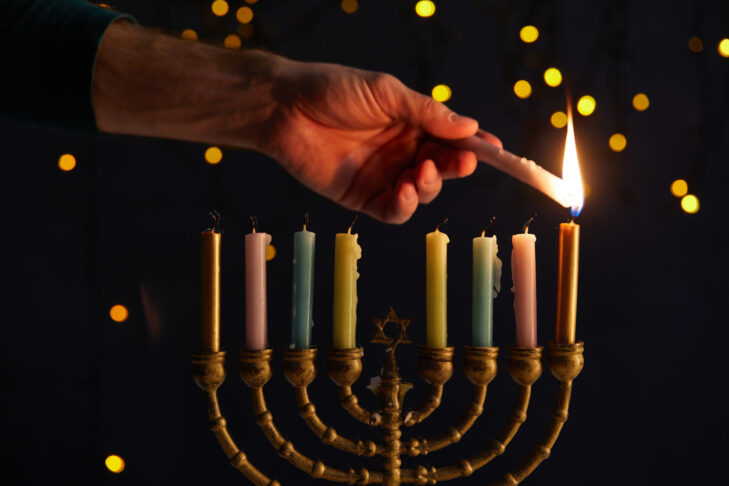 partial view of man lighting up candles in menorah on black background with bokeh lights on Hanukkah