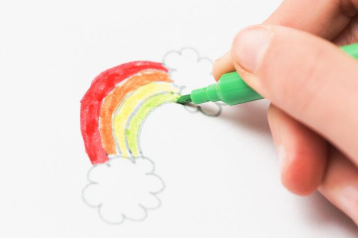 Little girl's felt-tip pen drawing a rainbow.