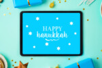 Jewish holiday Hanukkah concept with digital tablet mock up, menorah, sufganiyah and gift box over blue background