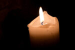 Flickering flame on wick of melted wax candle burning with black background and copy space. Paraffin candle flame in darkness. Background of remembrance or holiday celebration