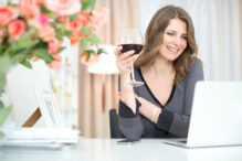 Woman sitting at the table with laptop and glass of red wine. Online dating.