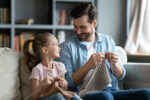 Smiling young father and little preschooler daughter sit on couch in living room knit with needles together, happy dad and small girl child have fun involved in favorite hobby family activity at home