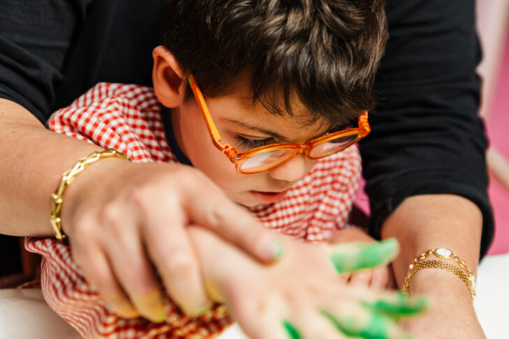 a disabled boy is painting his birthday wreath with his hands with the help of the teacher. you see the table, the brush, acrylic paint colors green, yellow, red.plastic art exercises.
