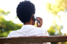Rear portrait of young woman sitting on a park bench and talking on mobile phone