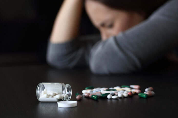 Close up of a depressed woman beside a lot of pills on a table on a dark background