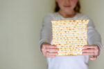 Young girl holding matzah or matza. Jewish holidays Passover invitation or greeting card.Selective focus.Copy space.
