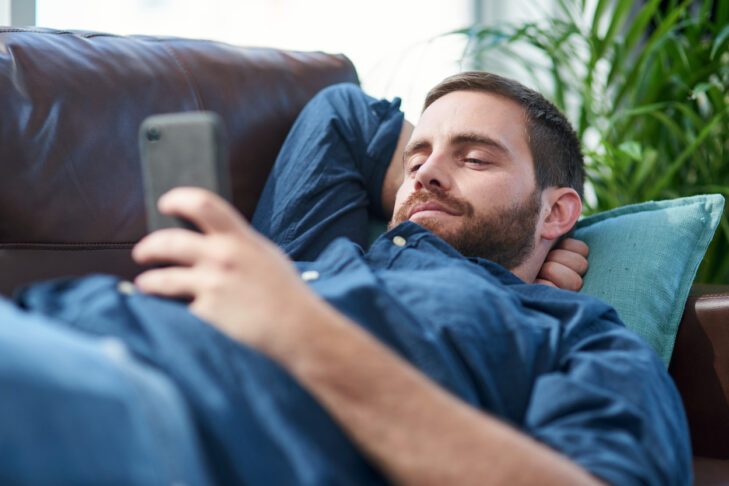 Shot of a young man using a smartphone while relaxing on a sofa