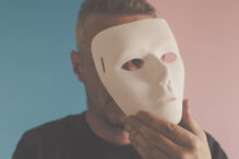 Man hiding his identity and feelings.  Photo is taken with full frame dslr camera indoors.