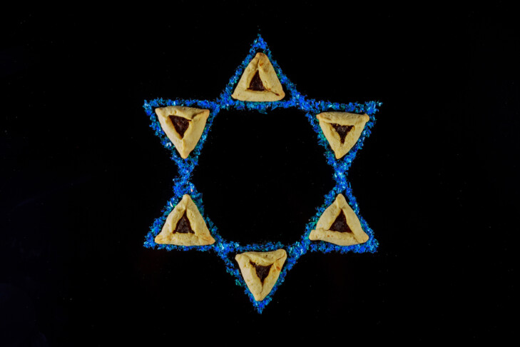 Jewish holiday background with hamantaschen cookies and star of David for Purim.