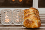 Jewish Sabbath with challah handmade tasty bread and candle.