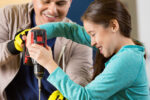 Mid adult Hispanic father teaches daughter how to use power drill in workshop. The elementary age girl smiles confidently as she uses the drill. The man is wearing fingerless gloves