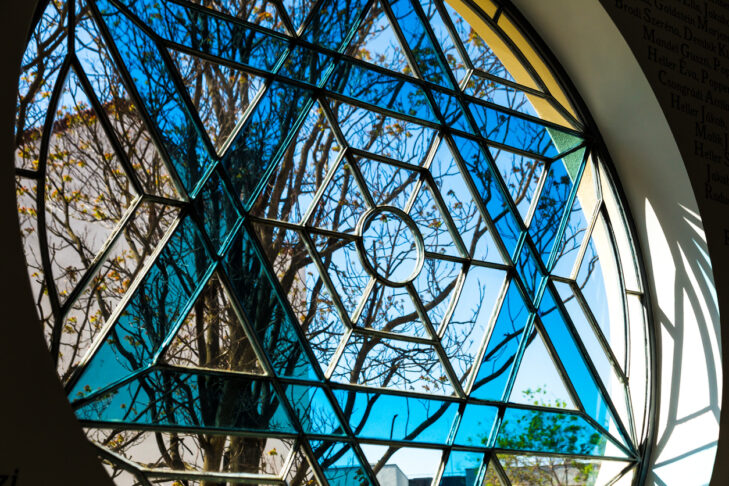 Close up color image depicting a Jewish Star of David stained glass window inside a synagogue. Room for copy space.