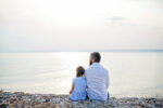 Rear view of father and small daughter on a holiday sitting by the lake or sea.