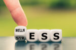 "Wellness instead of stress. Hand turns a dice and changes the word ""stress"" to ""wellness""."