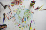 Photo from above of paper with kids drawings and doodles.