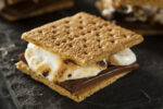 Close up image of S'mores dessert with roasted marshmallows and a chocolate bar sandwiched between two square graham crackers.  The dessert is displayed on a dark gray background, with two more S'mores in the background.  The background is slightly out of focus.